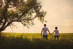 Pares felices que se colocan en el campo en la puesta del sol imagen de archivo libre de regalías