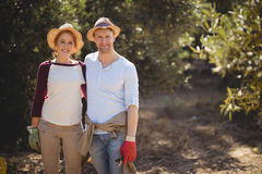 Pares felices que se colocan en la granja verde oliva el día soleado Imagen de archivo libre de regalías