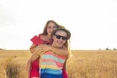 Pares felices que se divierten al aire libre en campo Concepto de la libertad piggyback fotografía de archivo libre de regalías