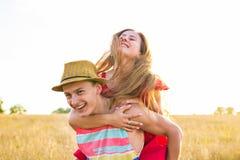 Pares felices que se divierten al aire libre en campo Concepto de la libertad piggyback imagen de archivo