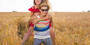 Pares felices que se divierten al aire libre en campo de trigo Familia alegre de risa junto Concepto de la libertad piggyback foto de archivo libre de regalías