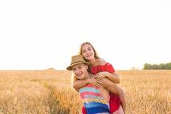 Pares felices que se divierten al aire libre en campo de trigo Familia alegre de risa junto Concepto de la libertad piggyback imagen de archivo