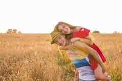 Pares felices que se divierten al aire libre en campo de trigo Familia alegre de risa junto Concepto de la libertad piggyback imagenes de archivo