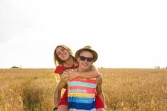 Pares felices que se divierten al aire libre en campo de trigo Familia alegre de risa junto Concepto de la libertad piggyback imágenes de archivo libres de regalías
