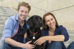 Pares felices que se divierten con el perro Fotos de archivo libres de regalías