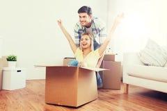 Pares felices que se divierten con las cajas en el nuevo hogar Fotografía de archivo libre de regalías