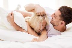Pares felices que se divierten en cama en casa Imagenes de archivo