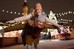 Pares felices que se divierten en el mercado de la Navidad Fotografía de archivo libre de regalías