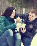 Pares felices que se divierten en el parque del invierno que bebe té caliente Imágenes de archivo libres de regalías