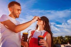 Pares felices que se divierten en la ciudad en la puesta del sol Hombre joven y mujer de risa que sostienen las tazas de café Fotos de archivo libres de regalías