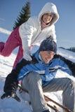 Pares felices que se divierten en la nieve Imágenes de archivo libres de regalías