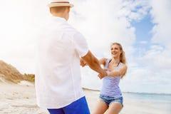 Pares felices que se divierten en la playa Foto de archivo