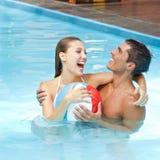 Pares felices que se divierten en piscina Imagenes de archivo