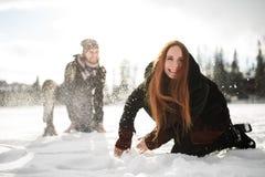 Pares felices que se divierten que juega en la nieve Imagen de archivo libre de regalías