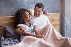 Pares felices que se enfrían hacia fuera en la cama junto Foto de archivo libre de regalías