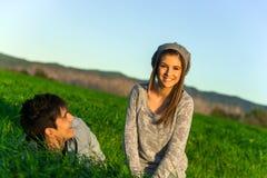Pares felices que se relajan en campo de hierba. Imagen de archivo libre de regalías
