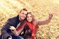 Pares felices que se relajan en el parque del otoño Imágenes de archivo libres de regalías