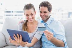 Pares felices que se relajan en el sofá que hace compras en línea con PC de la tableta fotos de archivo