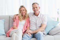 Pares felices que se relajan en el sofá que sonríe en la cámara Imágenes de archivo libres de regalías