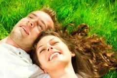 Pares felices que se relajan en hierba verde fotos de archivo libres de regalías