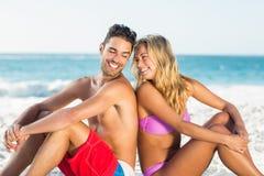 Pares felices que se sientan de nuevo a la parte posterior en la playa Imagenes de archivo