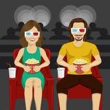 Pares felices que se sientan en el cine que mira la película 3D, comiendo las palomitas, sonriendo Fotografía de archivo libre de regalías