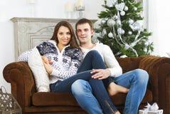 Pares felices que se sientan en el sofá por el árbol de navidad Fotos de archivo