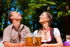 Pares felices que se sientan en jardín de la cerveza Imagen de archivo