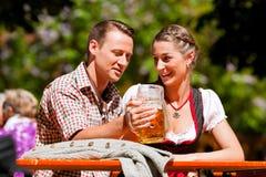 Pares felices que se sientan en jardín de la cerveza Foto de archivo libre de regalías