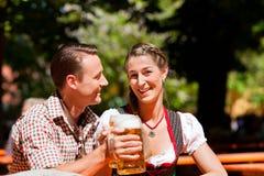 Pares felices que se sientan en jardín de la cerveza Fotografía de archivo libre de regalías