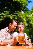 Pares felices que se sientan en jardín de la cerveza Foto de archivo