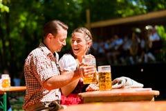 Pares felices que se sientan en jardín de la cerveza Imagenes de archivo