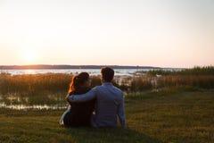 Pares felices que se sientan en la hierba que mira la puesta del sol delante de un lago fotografía de archivo libre de regalías