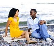 Pares felices que se sientan en la playa Imagen de archivo libre de regalías