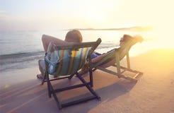 Pares felices que se sientan en las sillas del sol en la playa de Koh Samet en Fotos de archivo