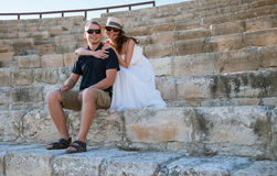 Pares felices que se sientan en los viejos pasos de piedra Fotografía de archivo libre de regalías