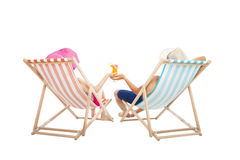 Pares felices que se sientan en sillas de playa foto de archivo