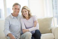 Pares felices que se sientan en Sofa In Living Room fotografía de archivo libre de regalías