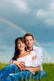 Pares felices que se sientan en un prado bajo el arco iris Imágenes de archivo libres de regalías