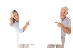 Pares felices que se sostienen y que señalan al cartel grande Imagenes de archivo