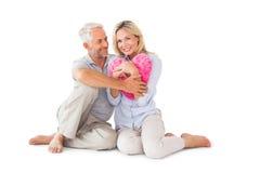 Pares felices que sientan y que sostienen la almohada del corazón Foto de archivo libre de regalías