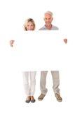Pares felices que sostienen el cartel grande Fotos de archivo