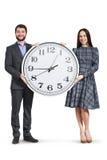 Pares felices que sostienen el reloj grande Foto de archivo libre de regalías