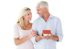 Pares felices que sostienen la casa modelo miniatura Fotografía de archivo