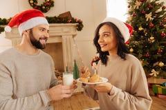 Pares felices que sostienen las galletas y la leche de harina de avena Imágenes de archivo libres de regalías
