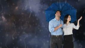 Pares felices que sostienen un paraguas debajo de la lluvia almacen de video