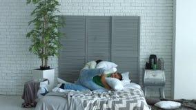 Pares felices que tienen lucha de almohada en el dormitorio almacen de metraje de vídeo