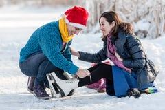 Pares felices que tienen patinaje de hielo de la diversión en pista al aire libre Imágenes de archivo libres de regalías