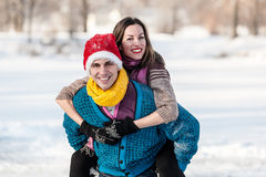 Pares felices que tienen patinaje de hielo de la diversión en pista al aire libre Imagen de archivo libre de regalías
