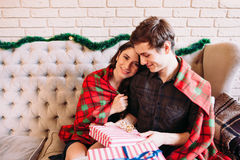 Pares felices que tienen resto cerca de los regalos de la Navidad Imagenes de archivo